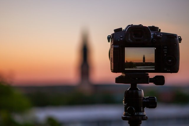 A DSLR camera taking photos of a church in the distance